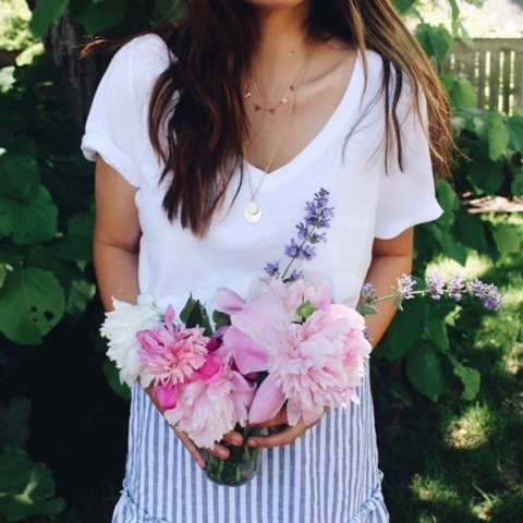 woman holding flowers, peonies, pink, layered necklace, garden